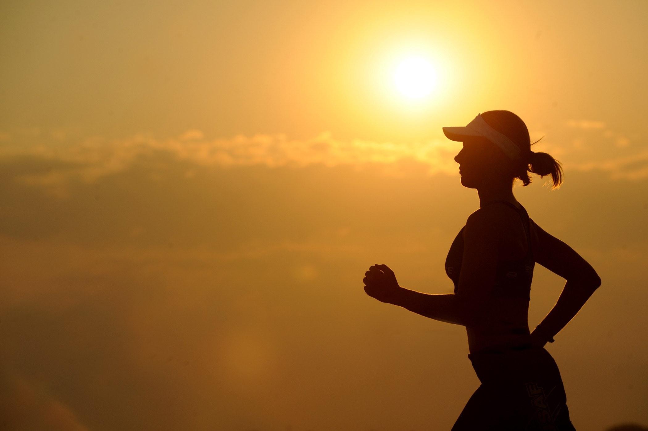 Kvinne jogger i solnedgang
